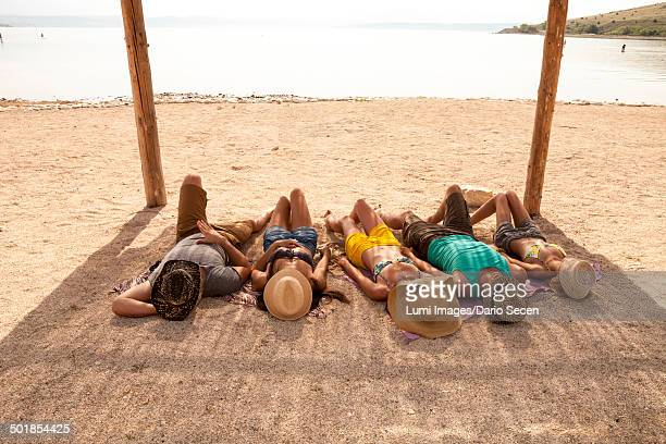 Croatia, Five young people on beach, relaxing side by side