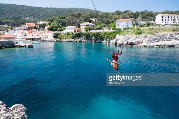 croatia, istria, losinj, rovenska, young man bungee jumping - adriatic sea stock pictures, royalty-free photos & images