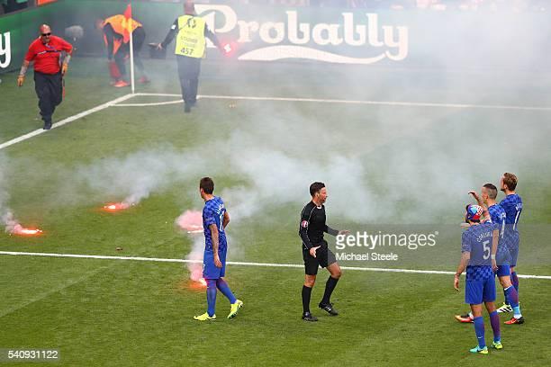 Croatia players surround referee Mark Clattenburg as flares are thrown onto the pitch during the UEFA EURO 2016 Group D match between Czech Republic...
