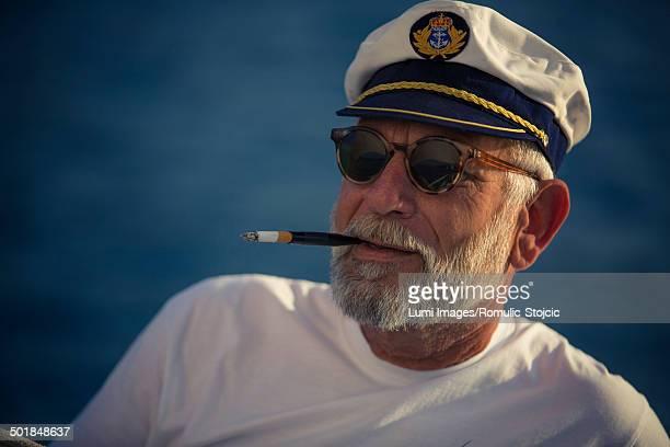 croatia, senior man with captain's hat smoking, portrait - sailor hat stock pictures, royalty-free photos & images