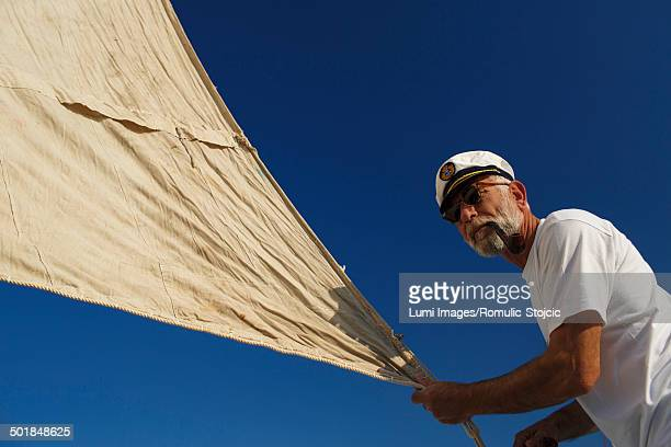 croatia, senior man with captain's hat steering sailboat - セーラーハット ストックフォトと画像
