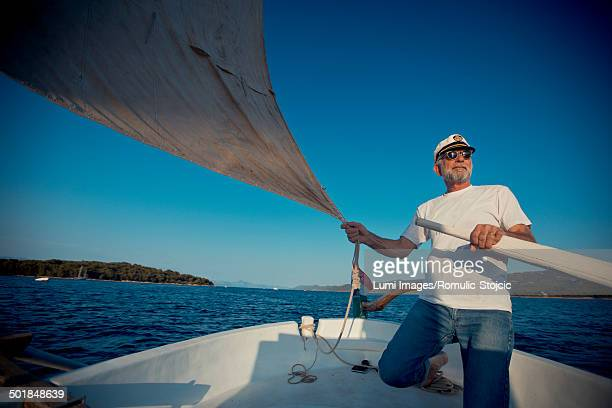 croatia, senior man with captain's hat steering sailboat - sailor hat stock pictures, royalty-free photos & images