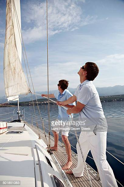 Croatia, Two young men on sailboat setting sail