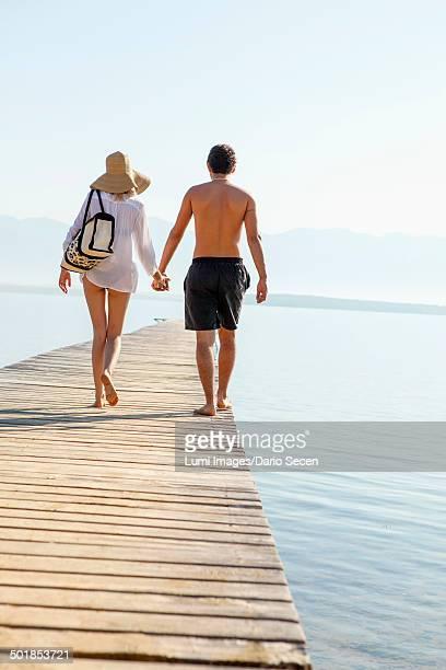 Croatia, Young couple in swimwear walking across boardwalk, rear view