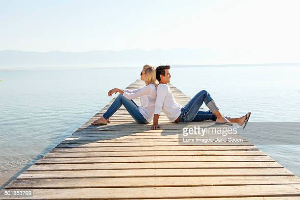 Croatia, Young couple relaxes on boardwalk by the sea