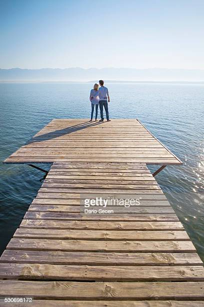 Croatia, Young couple stands on boardwalk, rear view
