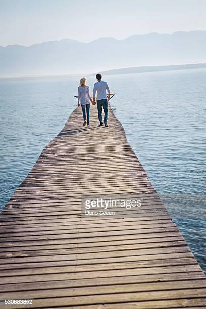 Croatia, Young couple walks across boardwalk, rear view
