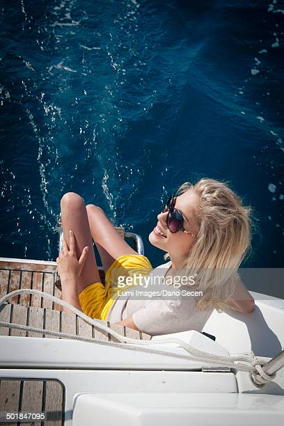 Croatia, Young woman sits on sailboat, directly above