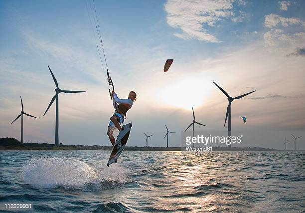croatia, zadar, kitesurfer jumping in front of wind turbine - windsurfing stock pictures, royalty-free photos & images