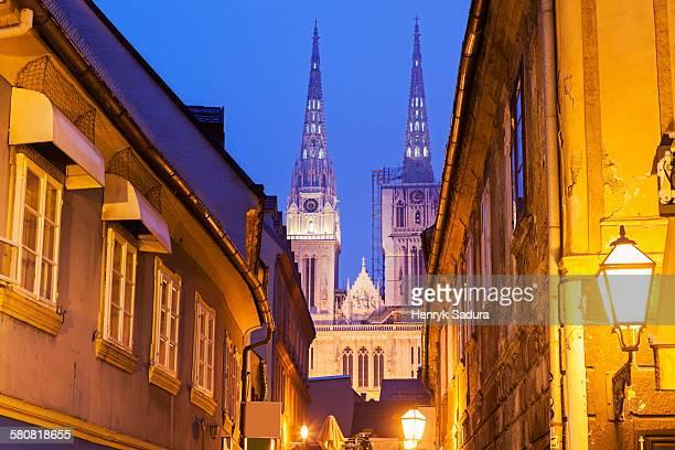 Croatia, Zagreb, Illuminated street and spires of Zagreb Cathedral