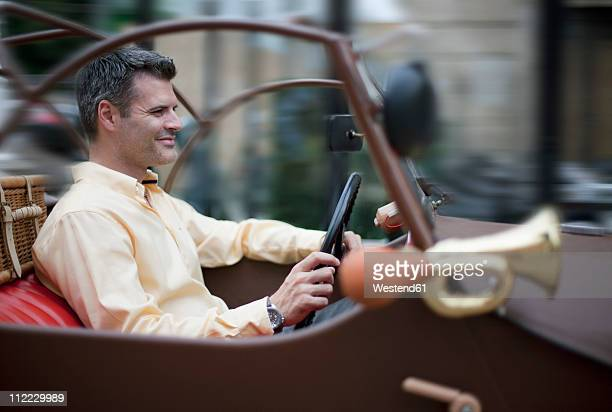 Croatia, Zagreb, Man in oldtimer car, smiling