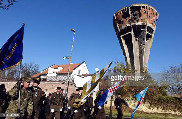 Croatian army officials carry war flags as they lead a procession which was called a 'Memory Column' through the eastern Croatian town of Vukovar on...