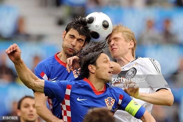 Croatian defender Vedran Corluka Croatian midfielder Niko Kovac and German defender Per Mertesacker head for the ball during their Euro 2008...