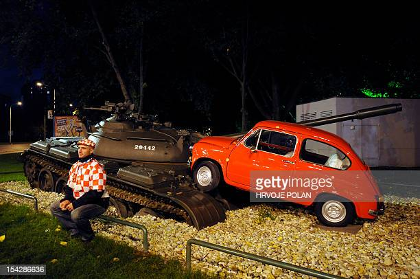 A Croatian football fan sits in front of an art installation showing a former Yugoslav National Army tank running over small red car in Osijek some...