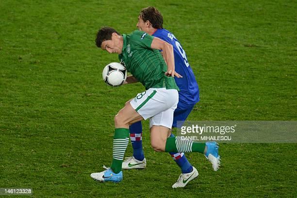 Croatian forward Nikica Jelavic vies with Irish midfielder Keith Andrews during the Euro 2012 football championships match Ireland vs Croatia on June...