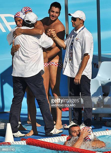 Croatian head coach Ratko Rudic jubilates with his players after beating US team at the end of the Men' water-polo Bronze-Medal match on August 1,...