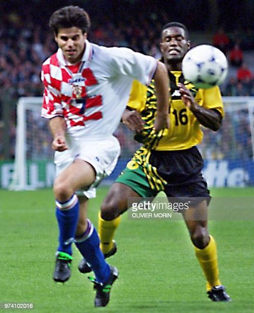 Croatian midfielder Aljosa Asanovic is challenged by Jamaican midfielder Robert Earle who scored the 11 equalizer for his team 14 June at the Felix...