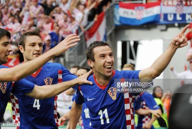 Croatian midfielder Darijo Srna celebrates with teammates defenders Vedran Corluka and Robert Kovac after scoring the opening goal against Germany...