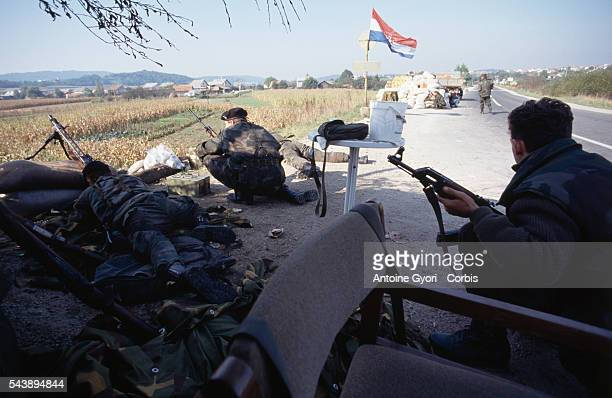 Croatian militiamen position themselves on the road near Karlovac while fighting against the Yugoslavian Army for the control of the city, which lies...