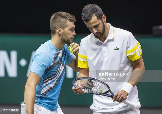 Croatian nationals Mate Pavic and team mate Nicola Mektic discuss during their match against France's Pierre Hugues Herbert and Germany's Jan Lennard...