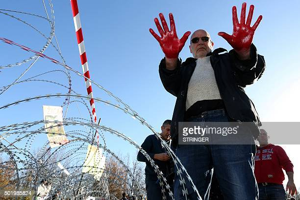 Croatian poet Nenad Popovic shows his hands covered in red paint symbolising blood as he stands next to a razorwire fence on Lucija Brezovica the...
