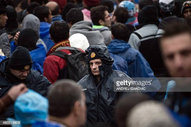 Croatian police officers stand guard as migrants wait to enter Croatia from the SerbiaCroatia border near the western Serbian village of Berkasovo on...