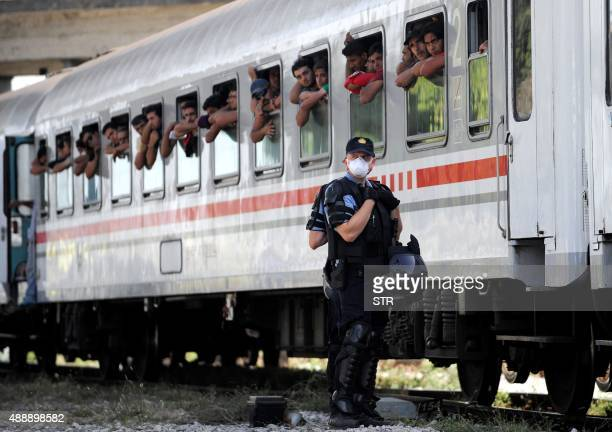 Croatian Police stand on the sidings beside a train carrying migrants and refugees in a marshalling yard near Zagreb on September 18 2015 A special...