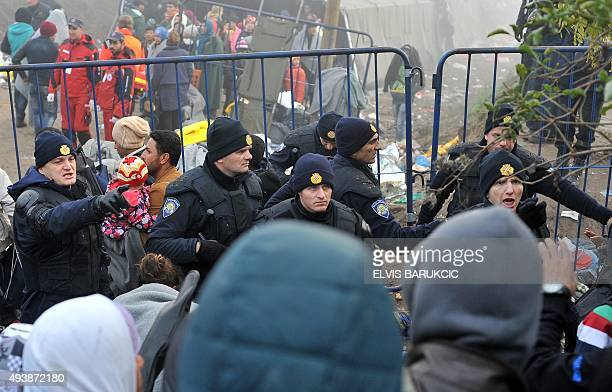 Croatian policemen contain a crowd of MiddleEastern migrants waiting to cross the SerbianCroatian border near the village of Berkasovo close to the...