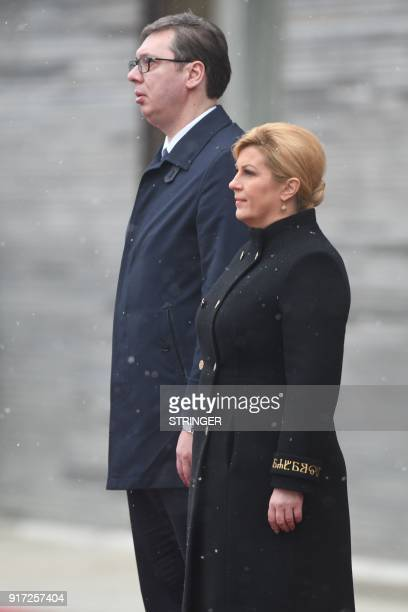Croatian President Kolinda Grabar Kitarovic and her Serbian counterpart Aleksandar Vucic listen to the national anthem during a welcoming ceremony at...