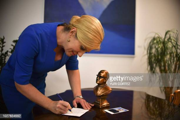 Croatian President Kolinda Grabar Kitarovic signs autographs next to a bust of Salvadoran Archbishop Oscar Arnulfo Romero who will be made a saint by...