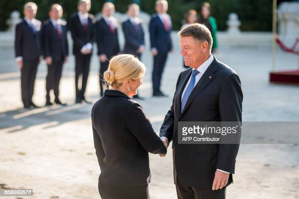 Croatian President Kolinda GrabarKitarovic and her Romanian counterpart President Klaus Iohannis shake hands during a welcome ceremony at Cotroceni...