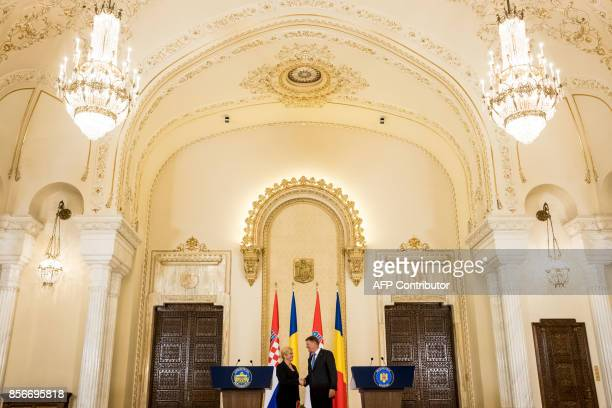 Croatian President Kolinda GrabarKitarovic and her Romanian counterpart President Klaus Iohannis shake hands after a joint press conference at...