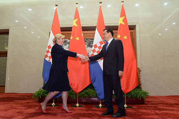 Croatian President Kolinda Grabar-Kitarovic approaches to shake hands with Chinese Premier Li Keqiang before their meeting at the Great Hall of the...