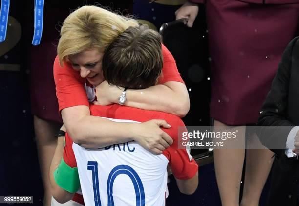 TOPSHOT Croatian President Kolinda GrabarKitarovic comforts Croatia's midfielder Luka Modric during the trophy ceremony at the end of the Russia 2018...