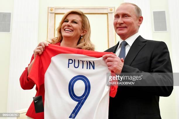 Croatian President Kolinda Grabar-Kitarovic offers to Russian President Vladimir Putin a jersey of the Croatian national football team bearing the...