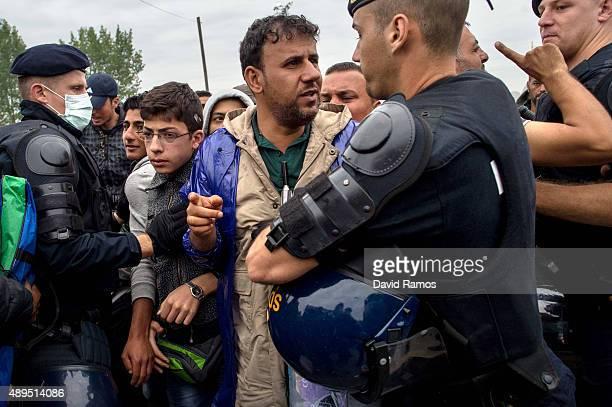 Croatian riot police officers control the access to a refugee camp as more migrants arrive from the Serbian border on September 22 2015 in Opatovac...