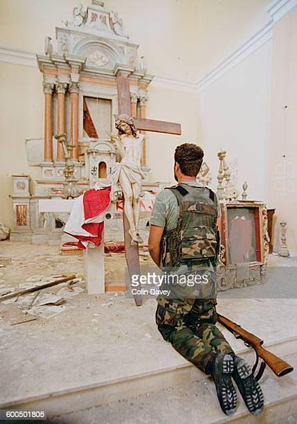A Croatian soldier praying in a ruined church in Knin following the capture of the city by Croatian forces during the Croatian War of Independence...