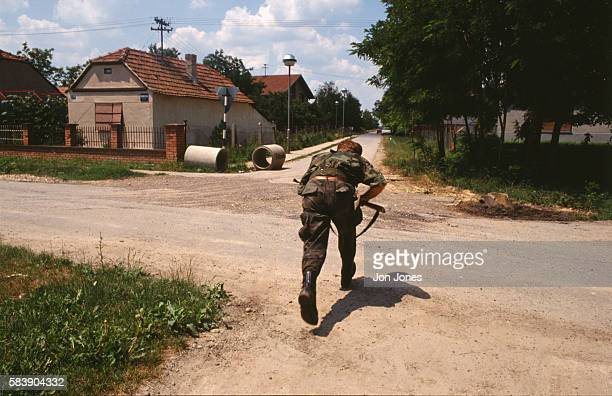 A Croatian soldier runs across the road in the suburbs of Vukovar