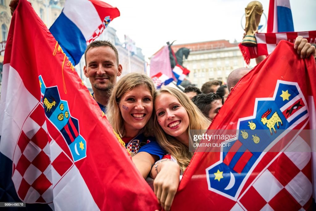 TOPSHOT - Croatian supporters hold national flags in downtown Zagreb on July 15, 2018, ahead of the 2018 Russia World Cup final football match between Croatia and France, the first final World Cup match ever in the history of Croatia.
