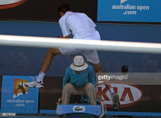 Croatian tennis player Marin Cilic vaults over a lines official during his men's singles quarterfinal match against US opponent Andy Roddick on day...