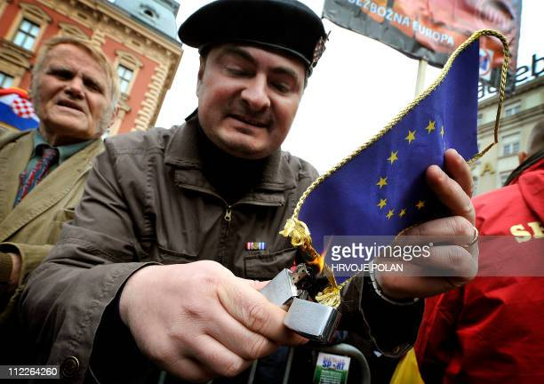 Croatian war veteran burns a small European Union flag during a protest in Zagreb's main square on April 16, 2011. Some 30,000 people gathered to...