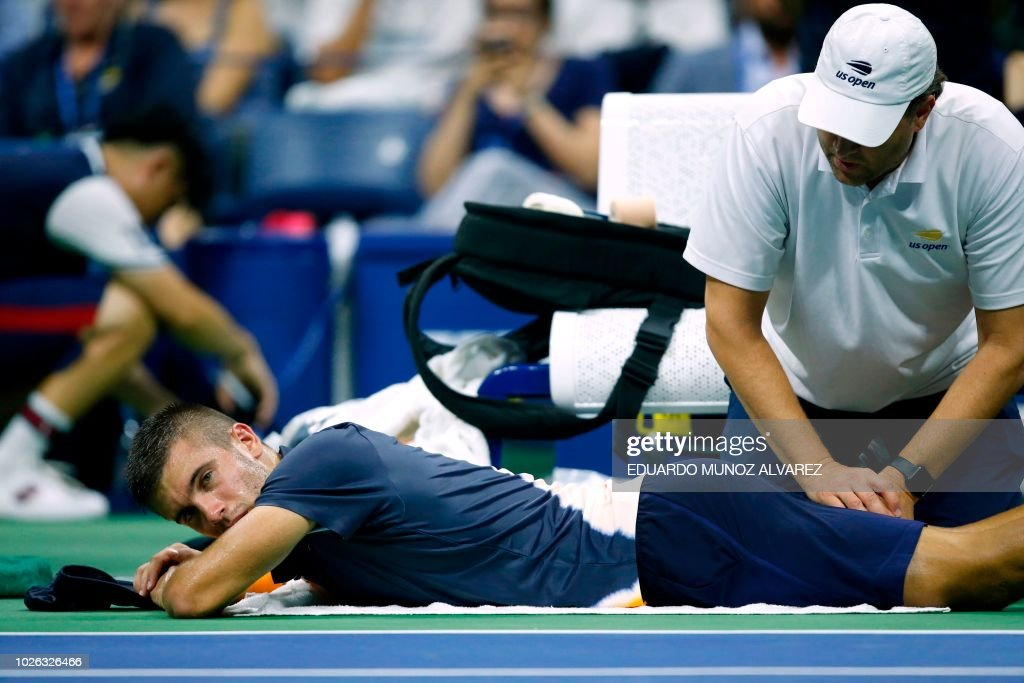 Croatia's Borna Coric receives medical attention during his men's singles tennis match against Argentina's Juan Martin del Potro on Day 7 of the 2018 US Open at the USTA Billie Jean King National Tennis Center on September 2, 2018 in New York City.