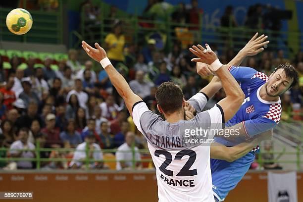 TOPSHOT Croatia's centre back Domagoj Duvnjak shoots past France's pivot Luka Karabatic during the men's preliminaries Group A handball match Croatia...