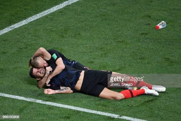 TOPSHOT Croatia's defender Dejan Lovren celebrates with Croatia's defender Domagoj Vida after winning the Russia 2018 World Cup semifinal football...