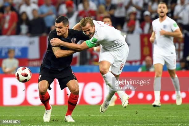 Croatia's defender Dejan Lovren challenges England's forward Harry Kane during the Russia 2018 World Cup semi-final football match between Croatia...