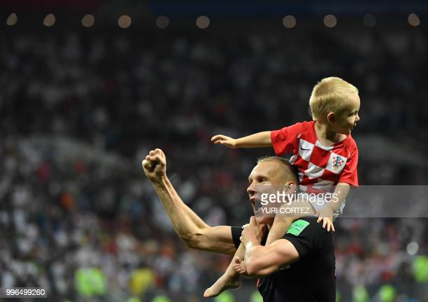 Croatia's defender Domagoj Vida celebrates with his son David at the end of the Russia 2018 World Cup semifinal football match between Croatia and...