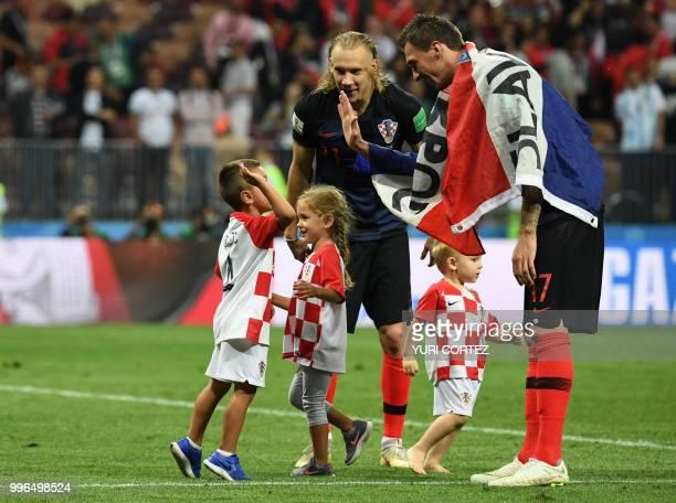 Croatia's defender Domagoj Vida standing with his son David and Croatia's forward Mario Mandzukic celebrate with the children of Croatia's forward...