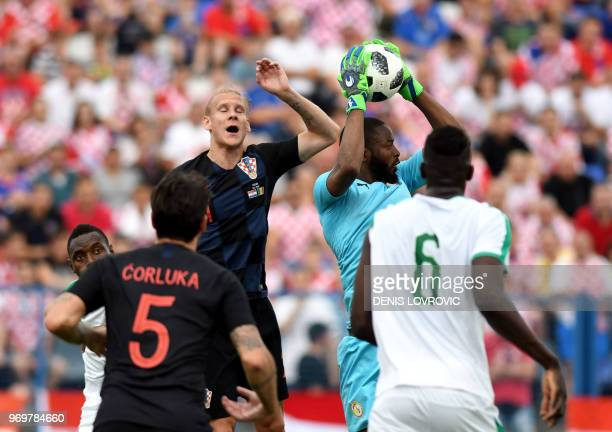 Croatia's defender Domagoj Vida vies with Senegals goalkepeer Diallo Abdoulaye during the international friendly football match between Croatia and...