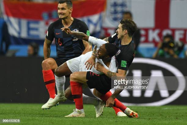 TOPSHOT Croatia's defender Sime Vrsaljko and Croatia's defender Dejan Lovren challenge England's forward Raheem Sterling during the Russia 2018 World...