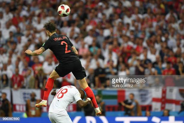 TOPSHOT Croatia's defender Sime Vrsaljko heads the ball over England's defender Ashley Young during the Russia 2018 World Cup semifinal football...